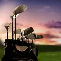 Golf clubs with sunset backdrop